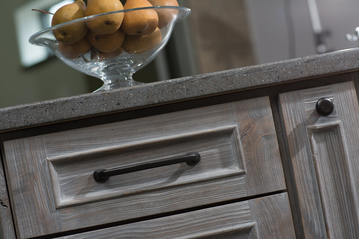 A close up of driftwood inspired weathered wood cabinets from Dura Supreme Cabinetry with a light gray stain.