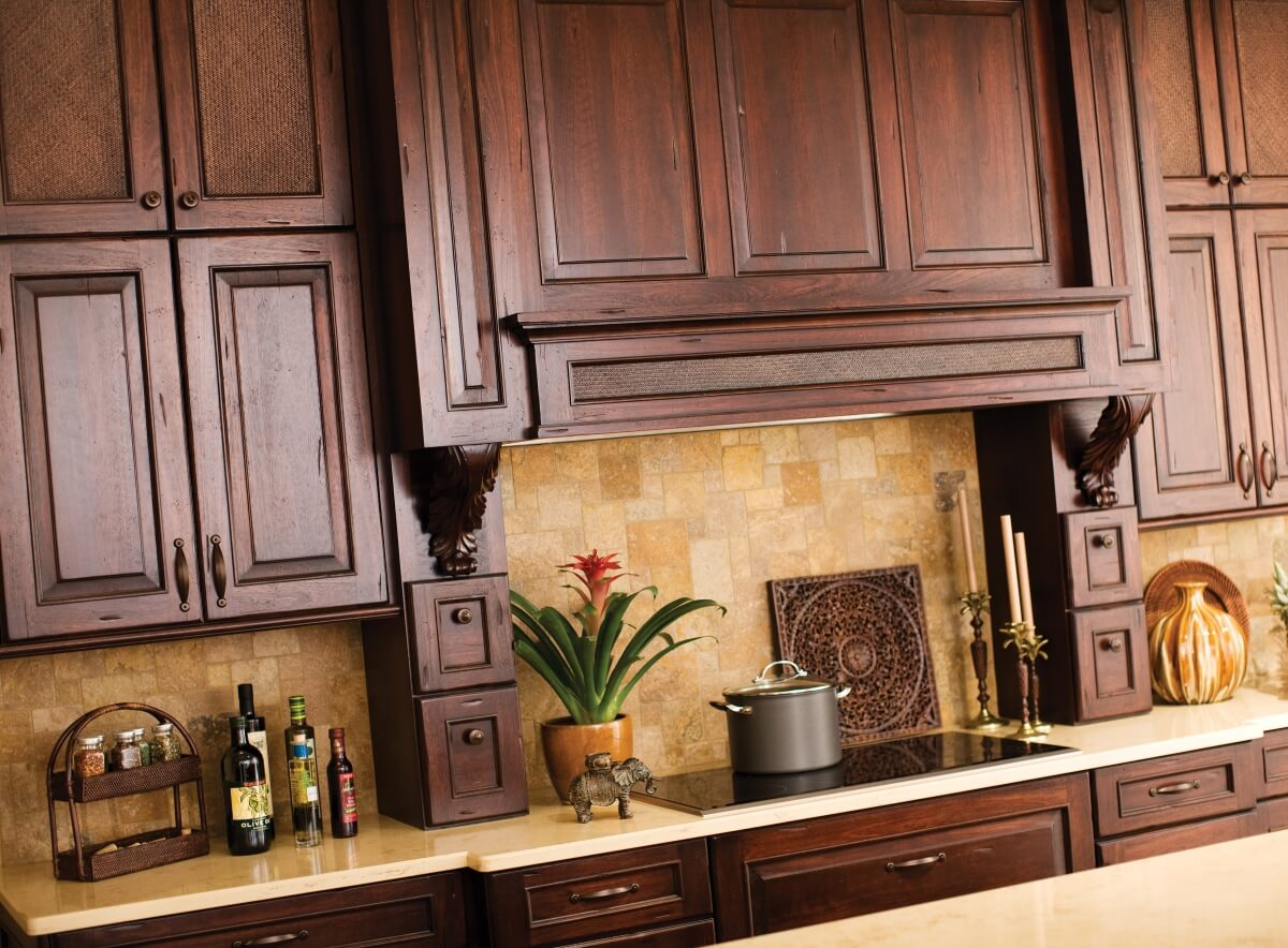 Grand wood hoods with intricate detail create a stunning focal point for a West Indies kitchen.