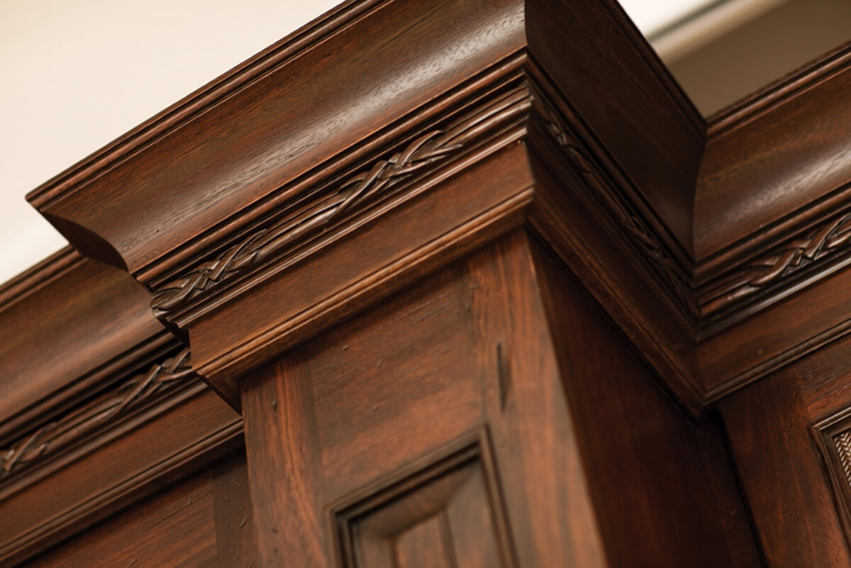 Close up of the top molding on tropical styled kitchen cabinets. An intricate carved molding accents the molding stack.