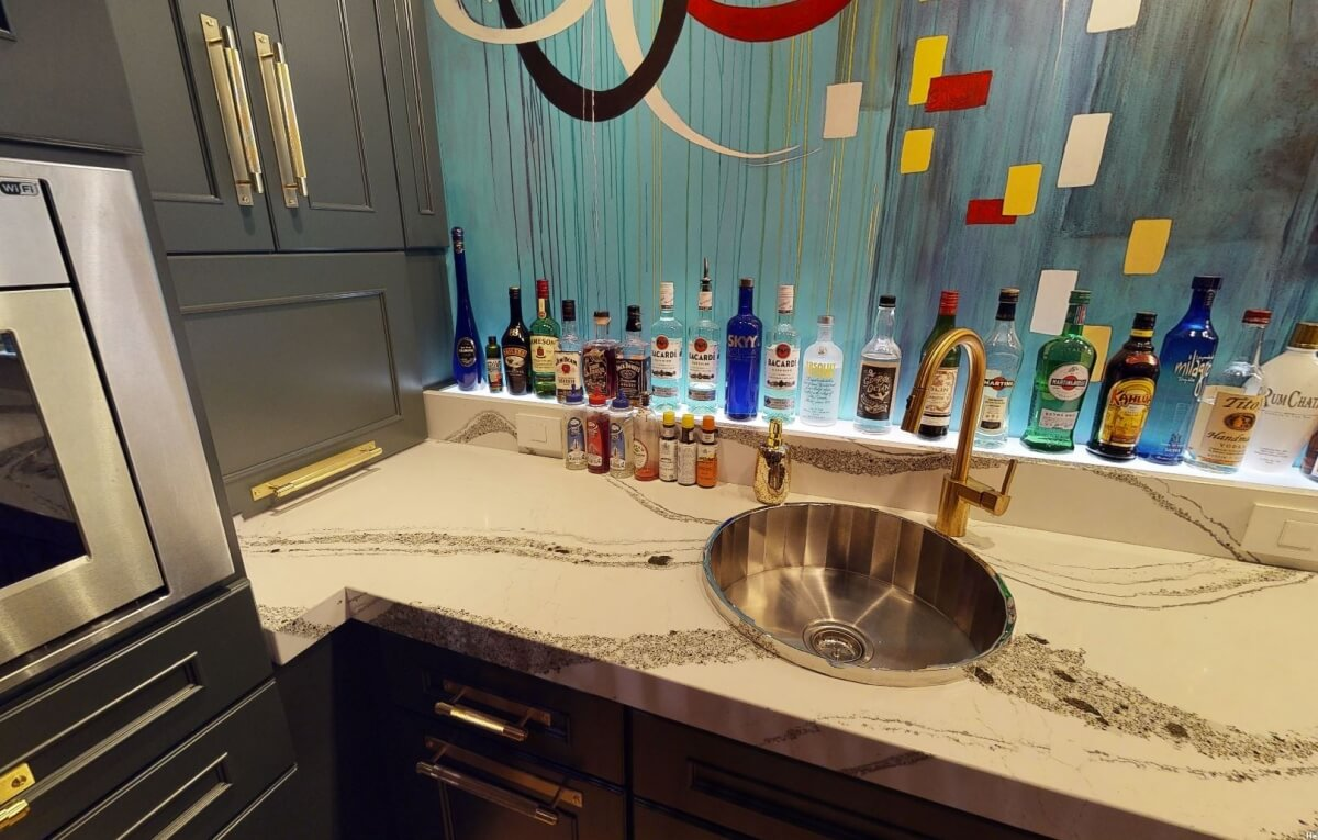 A decorative wet bar sink with a mirror look is a like a jewel in this wet bar remodel design.