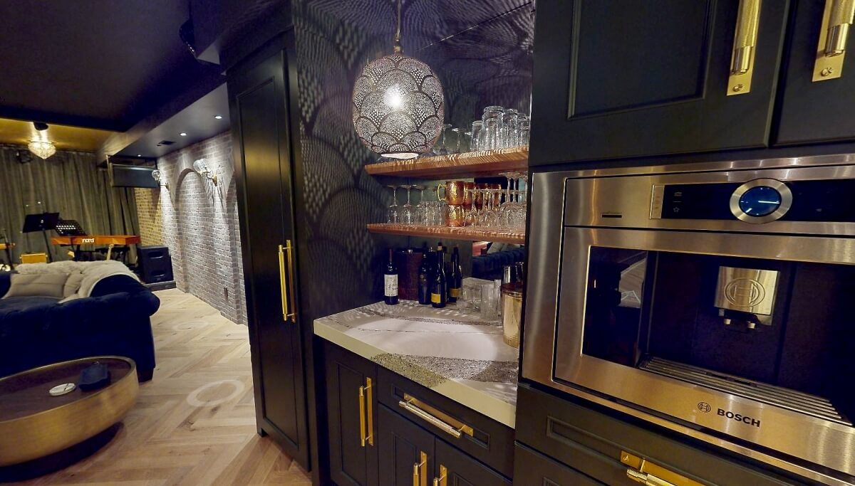 A close up of reflective lights on a mirror backsplash with dark green cabinets in a home bar. A newly remodeled basement design for entertaining.