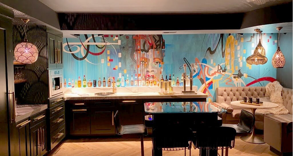 A stunning modern and trendy urban basement remodel with a dark green wet bar and bright colorful artwork.