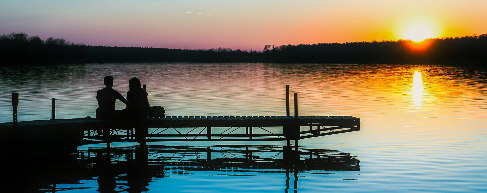 A couple sitting on the end of the dock at their lake house.