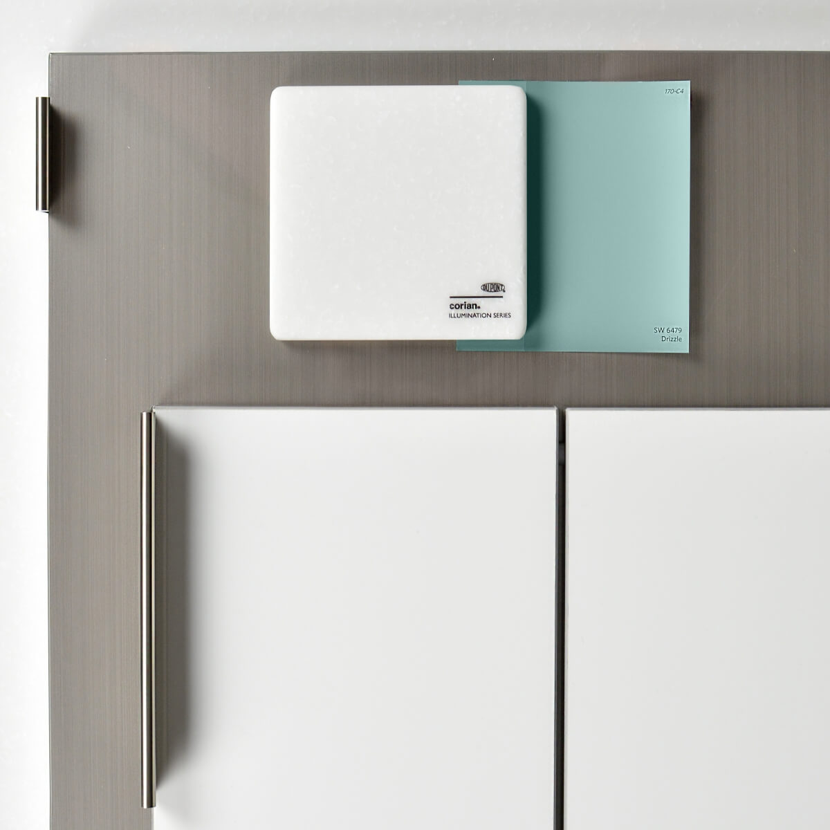 This design concept combines Dura Supreme's Ava-2T door in White Acrylic and Talia door in Wired Mercury with Corian countertop in Arctic Ice and Sherwin-Williams paint color Drizzle SW 6479.