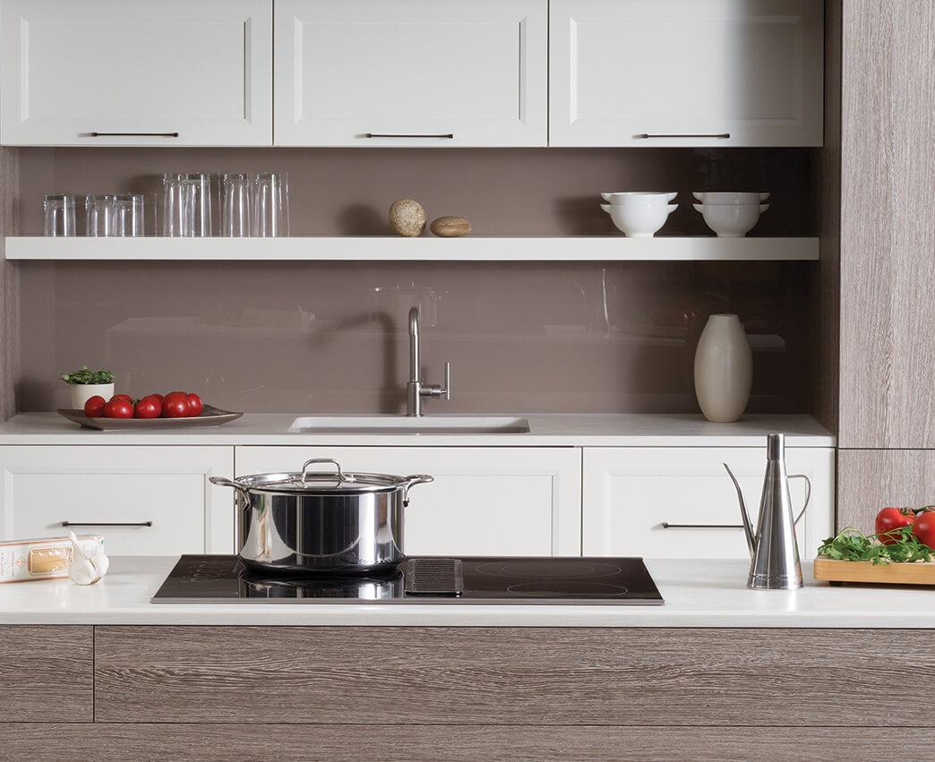 A modern styled Dura Supreme kitchen with an electric cooktop. A modern kitchen with textured foil and white painted cabinets.