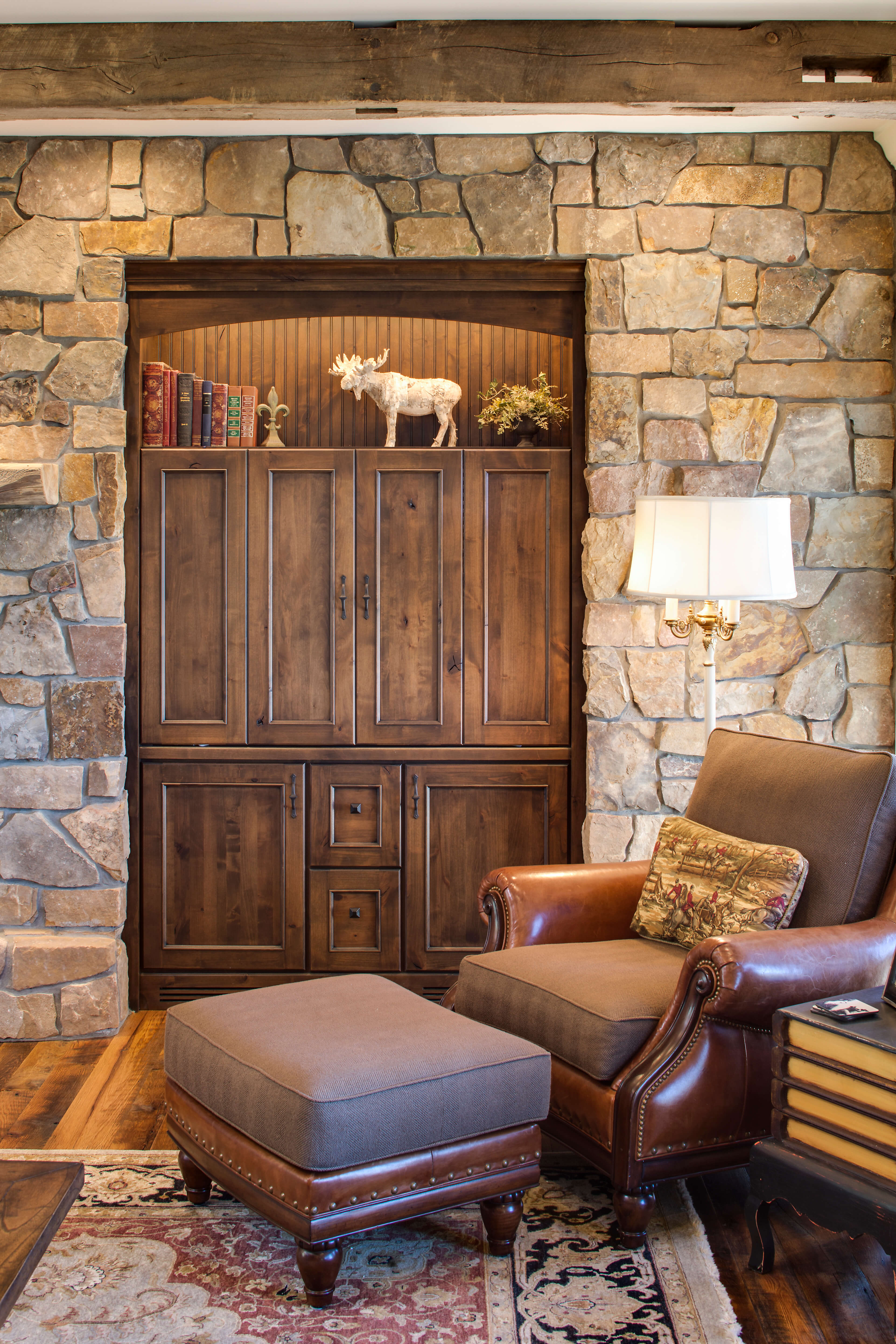 Rustic Knotty Alder Cabinets tucked into a stone wall for additional cabinet storage in a living room.