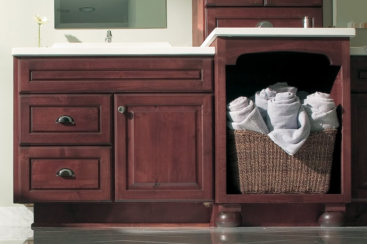 An open cabinet in a bathroom vanity with storage for towels or a laundry basket.