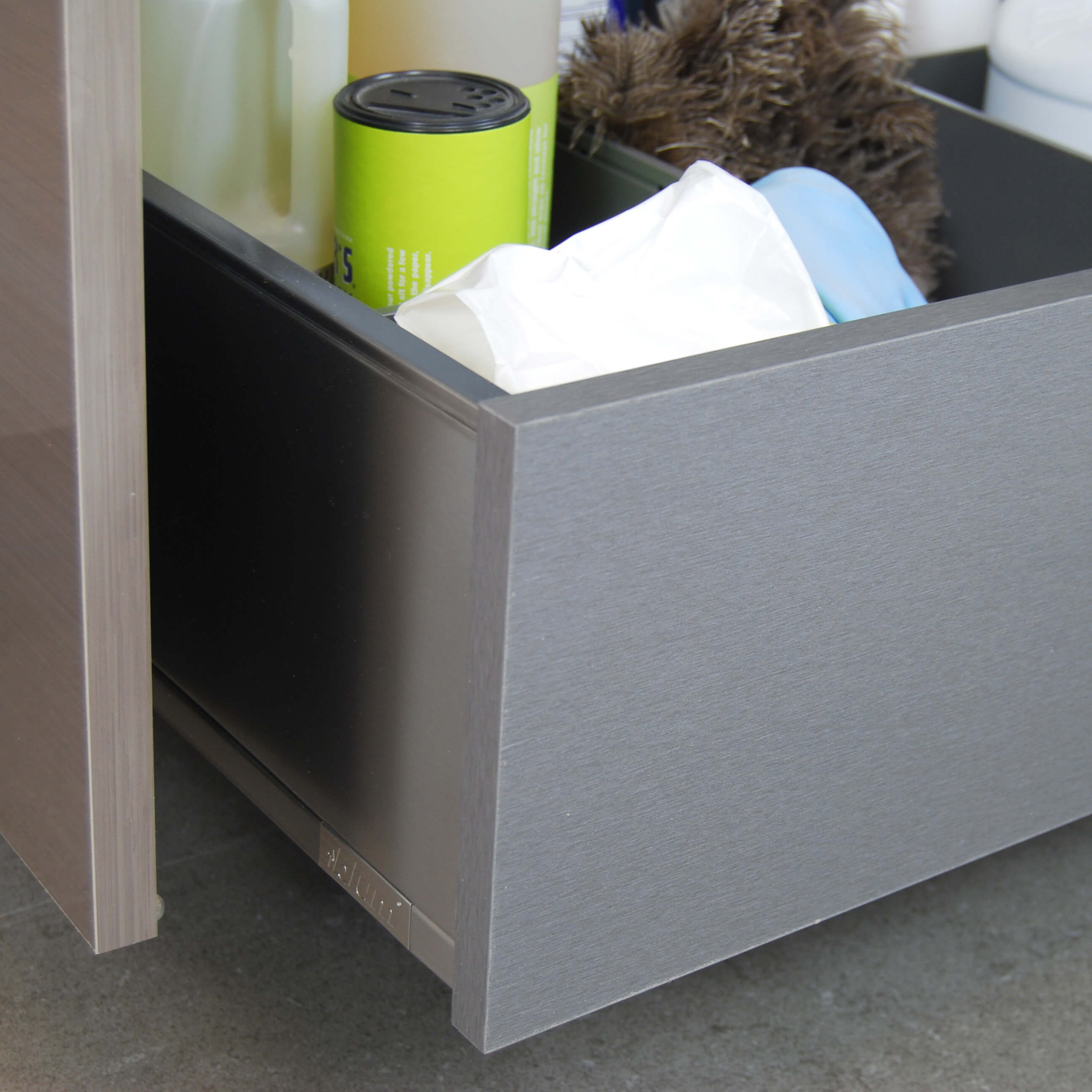 A standard wood roll-out or a stainless steel roll-out from Dura Supreme offers easy to access storage under the sink for organizing and storing cleaning supplies.