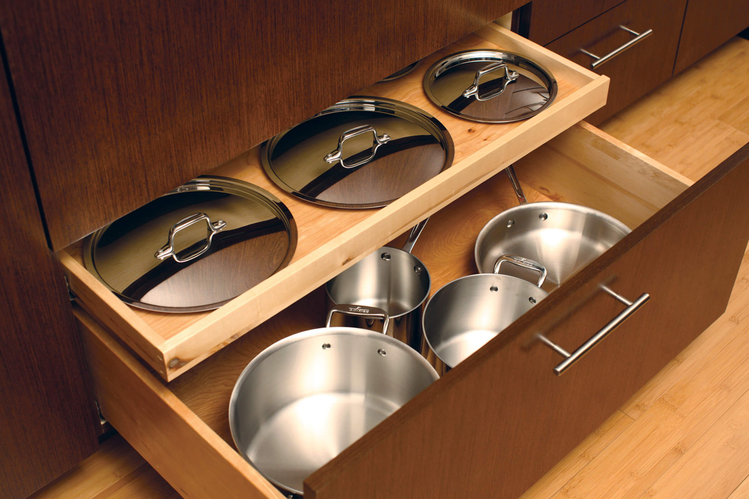 A Shallow Roll-Out Above Drawer neatly stores the lids for the pots and pans that are stored in the deep drawer below.