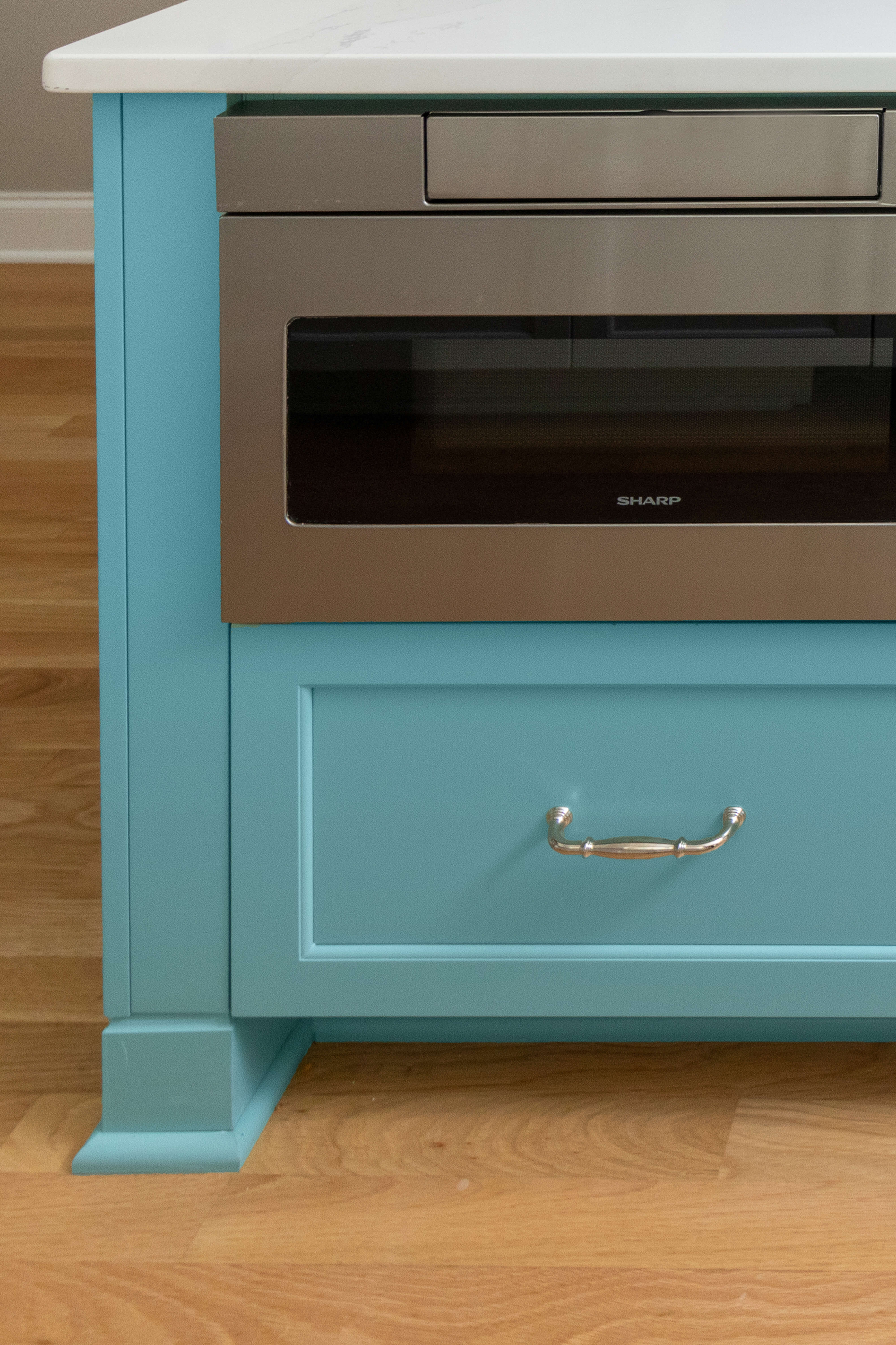 A light blue painted kitchen island with furniture style feet and styled toe space.