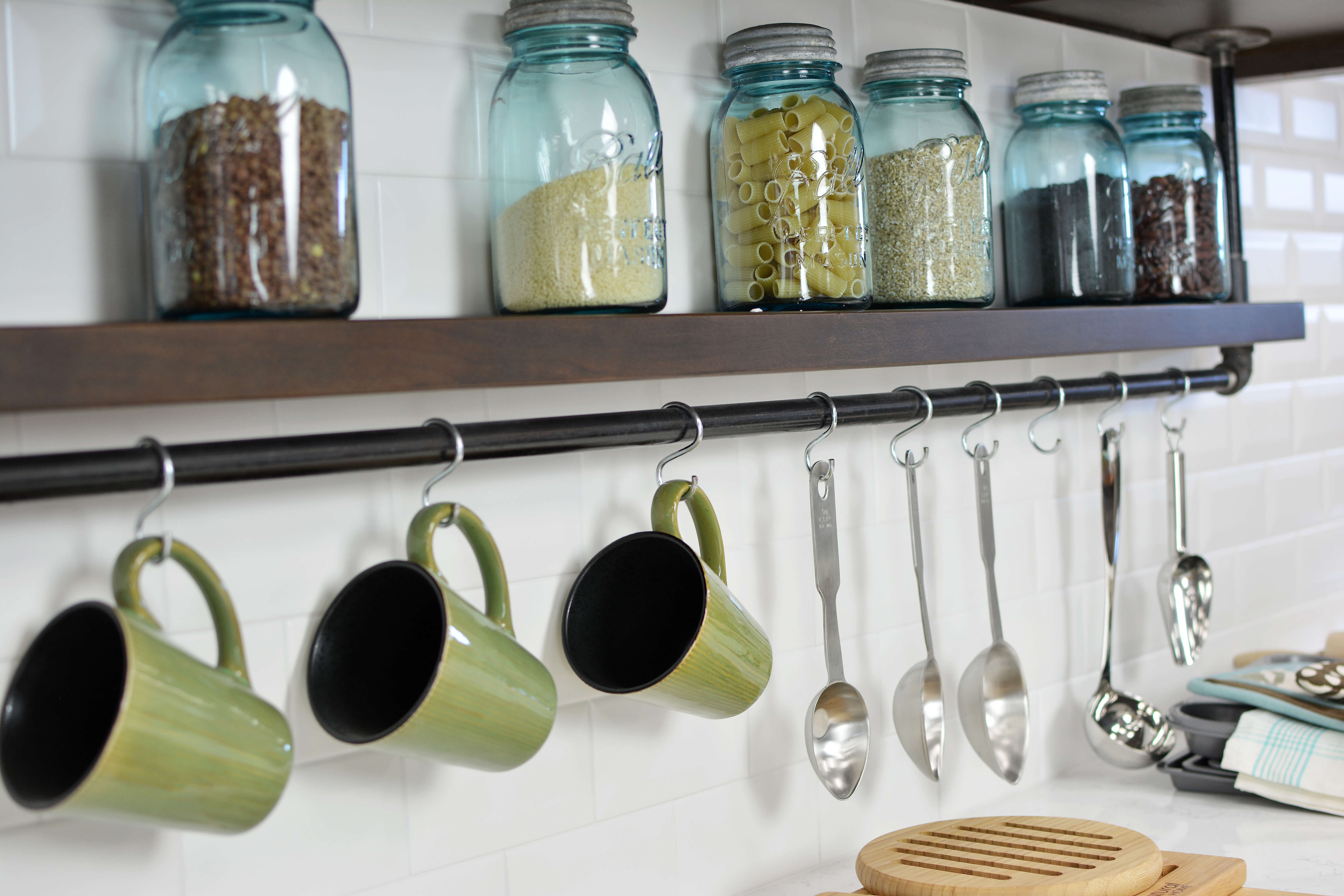 • In this kitchen, an industrial style shelf hangs from the wall cabinets with hanging coffee cup storage. This feature is placed strategically within a close distance to the coffee station.